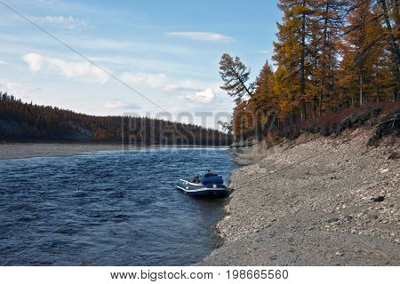 Boat near the shore of the Siberian river in the fall. Riverbed Moiyerokhan in Evenkia in September during the rafting and fishing Krasnoyarsk region Russia