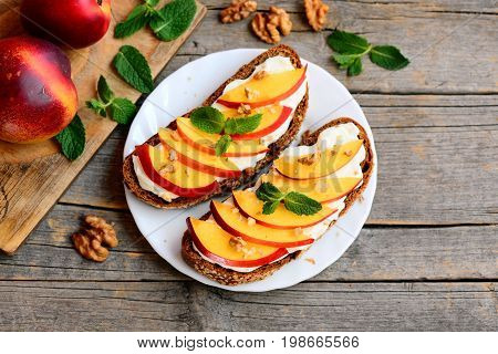 Healthy nectarine, walnuts and cream cheese sandwiches. Open sandwiches with cream cheese, ripe nectarine slices, walnuts and mint on a white plate and old wooden table. Summer snack recipe. Top view