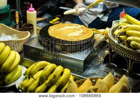 PATONG BEACH, THAILAND - 19 MAY 2017:: Nightlife in Thailand. Street food. A woman prepares a pancake with chocolate in the street.