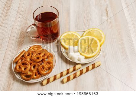 Transparent cup of black tea on a light table and saucers with pretzels sweet sticks and chopped lemon and pieces of refined sugar.