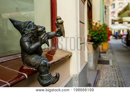 Wroclaw Silesia Poland - July 25 2017: Miniature bronze figure of a gnome who eats ice cream on the windowsill of an old confectionery in the city center.