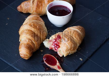 croissant buns and raspberry jam on a black background
