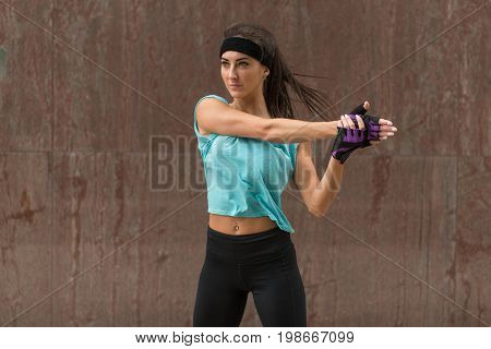 Female athlete stretching her arm. Young woman doing warm-up exercises before running on the pavement of city street.