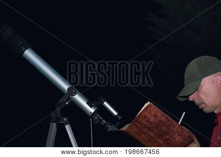Man making drafting or drawing with a book in hands sitting next to amateur telescope