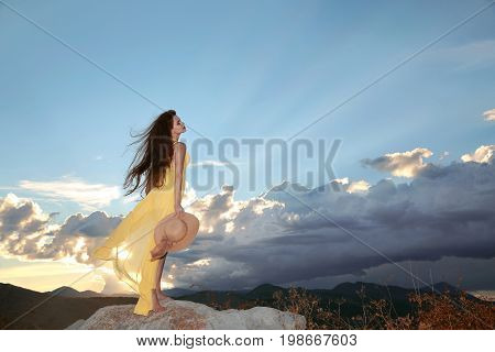 Enjoyment. Free happy woman enjoying sunset. Beauty Girl over Sky clouds and Sun. Beautiful brunette in yellow dress with hat  enjoying peace, serenity in nature