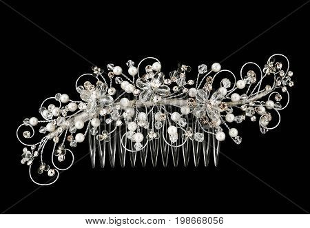 A hair comb studded with faux white  flowers, leaves and pearls. Fit for a bride on her wedding day or other formal event.