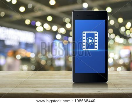 Play button with movie icon on modern smart phone screen on wooden table over blur light and shadow of shopping mall Cinema online concept