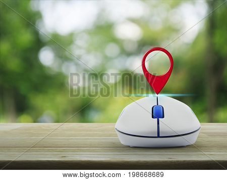 Map pin location button with wireless computer mouse on wooden table over blur green tree in park Map pointer navigation concept