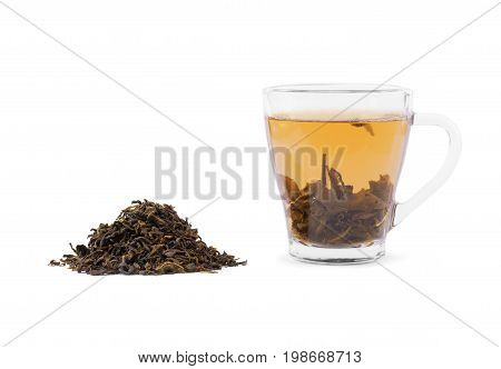 A transparent cup of traditional chinese green tea isolated on a white background. Hot, delicious and healthful black tea in a mug. A pile of dry and aromatic tea leaves. Herbal tea for a breakfast.