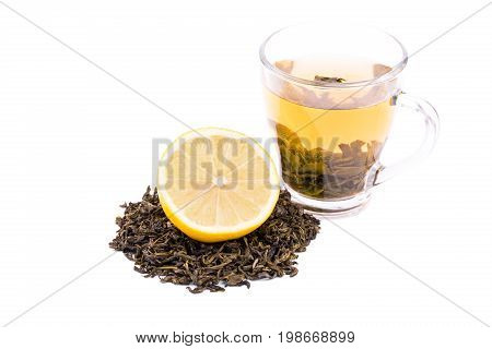 A close-up of a glass tea cup full of green tea isolated on a white background. A cup with hot yellow liquid, cut lemon and a heap of green tea leaves. Autumn organic beverage. Healthful herbal tea.
