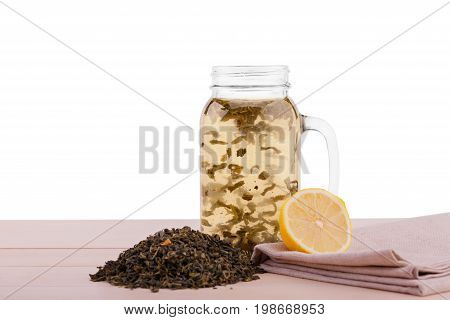 A sweet black tea and a cut lemon isolated on a white background. Organic Chinese tea in a big and transparent mason jar with a hot drink. Herbal tea leaves and a lemon on a fabric on a table.