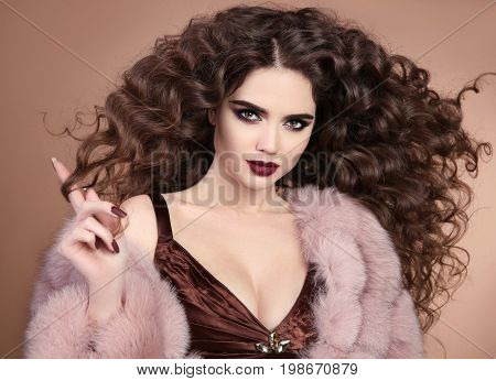 Hairstyle. Beauty hair. Fashion brunette girl with long curly hair, beauty makeup. Glamour portrait of beautiful brunette with marsala matte lips in pink fur coat isolated on beige background.