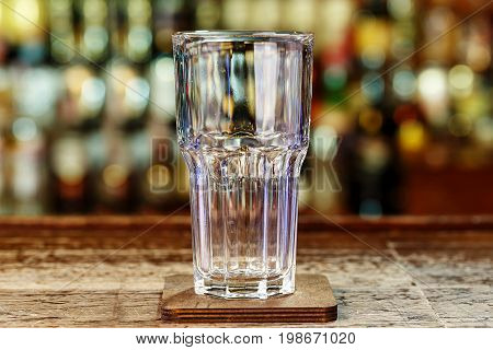 Clean beer glass on the bar space for text blurred background of the bar
