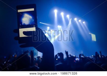 Close up of recording video with smartphone during a concert. Crowd at concert and blurred stage lights.