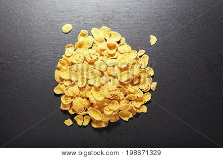 Corn flakes piled on a black background