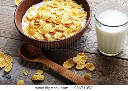 Cornflakes in a brown clay plate on a worn wooden background next is a glass of milk and a spoon and several flakes are scattered