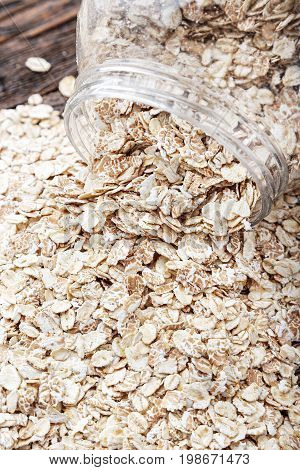 Inverted can of oatmeal on a wooden table. The oatmeal is scattered on the table . Healthy food for breakfast. Space for text