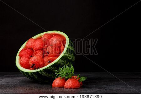 Colorful, fresh, cut watermelon on a black background. Red ripe watermelon scoops with seeds. A cut watermelon with bright mint leaves. Refreshing and healthful summer fruits and berries. Copy space.