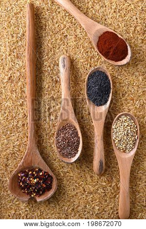 Top view of grains and spices on wooden spoons atop a bed of brown rice.