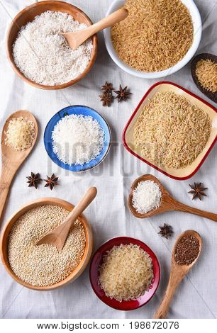 Top view of assorted grains in bowls on a white table cloth.