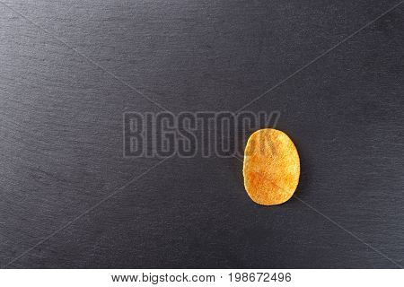 potato chips on a slate a traditional beer snack unhealthy eating. View from above place for text
