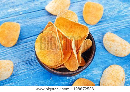 Crispy potato chips in a earthenware dish on blue kitchen table