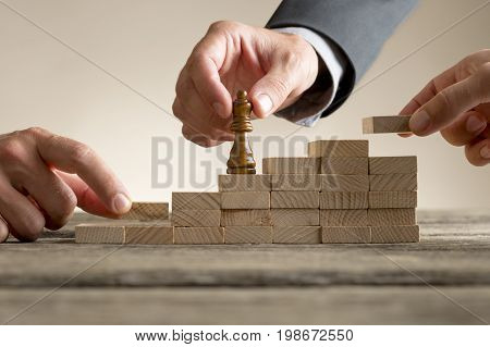 Business success and promotion concept with a businessman moving a chess piece up a series of steps formed by building blocks being put in place by his team in a close up view.