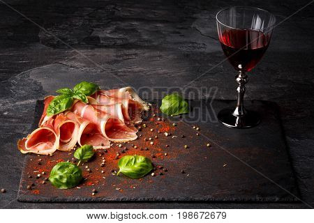 Beautifully sliced prosciutto and a glass of red wine on a black background. Appetizing traditional french wine with meaty restaurant snacks. Delicatessen, luxury, celebration concept. Copy space.