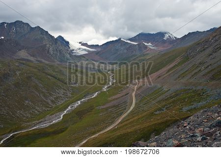 Downhill road from the pass to the valley of the river in the Tien Shan mountains Kyrgyzstan