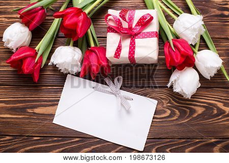 Wrapped box with present empty tag and bright red and white tulips flowers on wooden background. Selective focus. Place for text.