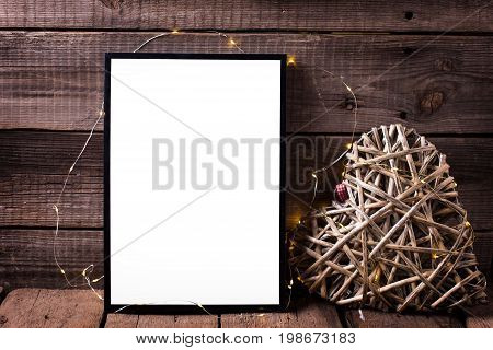 Empty black frame and decorative heart with twinkle light on aged wooden background. Place for text. Mock-up for design.