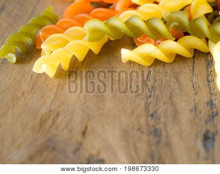 Background of colorful pasta texture close-up. close up of a dried italian pasta on a wooden table.Colored natural pasta