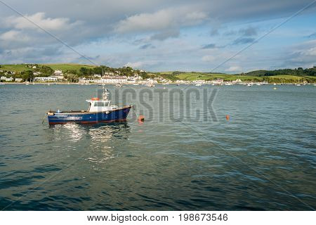 Painted blue motor boat for fishing moored to buoy in estuary at Appledore, Devon