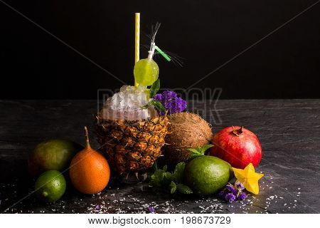 A big pineapple cup with multifruit juice and cracked ice on a saturated black background. Carambola, refreshing garnet, juicy coconut, green avocado with mint and violet flowers.