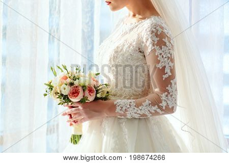 A Beautiful Bride Is Holding A Wedding Bouquet With White Roses And Peach Peonies On A Bright Window