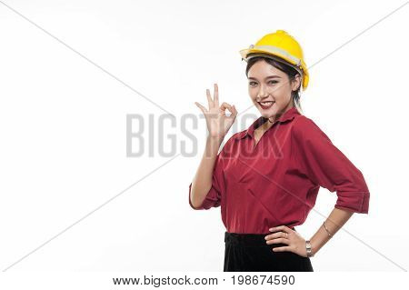 Asian woman engineer in red shirt and yellow safety cap making okay action. People gesturing in business and enginerring concept
