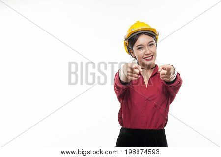 Asian woman engineer in red shirt and yellow safty cap pointing front with happy emotion. People gesturing in business and enginerring concept