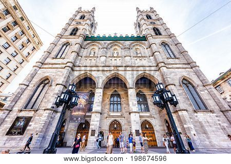 Montreal Canada - May 28 2017: Full front exterior view of Notre Dame Basilica in morning with people walking by in Quebec region city