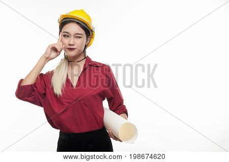 Young Asian woman architect with red shirt and yellow safety helmet thinking while carrying blueprints. Industrial occupation people concept