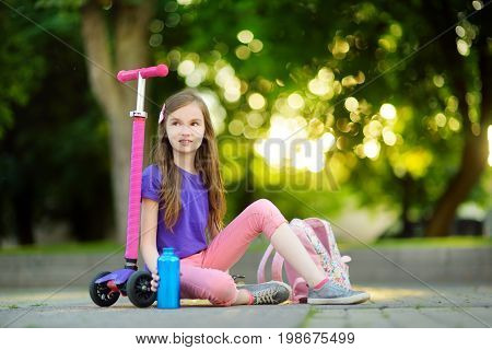 Little Child Learning To Ride A Scooter In A City Park On Sunny Summer Day. Cute Preschooler Girl In