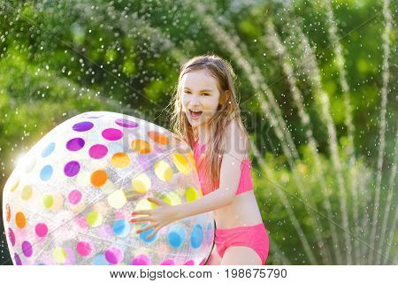 Adorable Little Girl Playing With A Sprinkler In A Backyard On Sunny Summer Day. Cute Child Having F