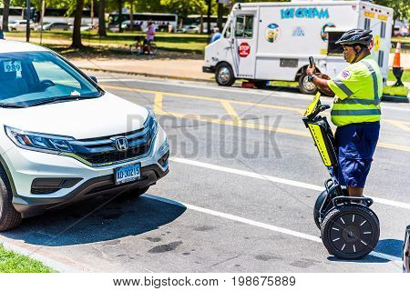 Washington DC USA - July 3 2017: Police traffic officer writing ticket for car illegally parked while riding segway on national mall