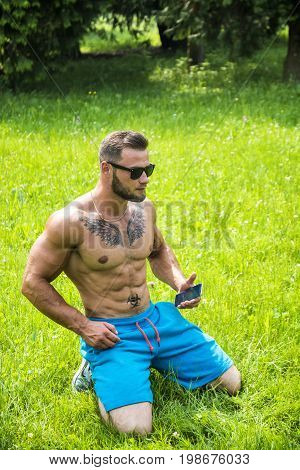 Handsome Muscular Shirtless Hunk Man Outdoor in City Park Sitting on Grass. Showing Healthy Muscle Body While Looking away