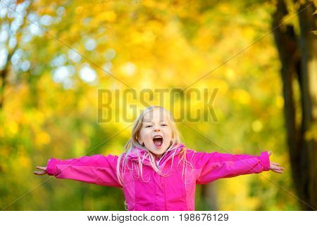 Cute Little Girl Having Fun On Beautiful Autumn Day. Happy Child Playing In Autumn Park. Kid Gatheri