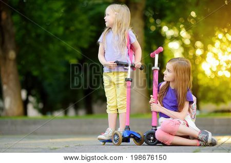 Small Children Learning To Ride Scooters In A City Park On Sunny Summer Evening. Cute Little Girls R