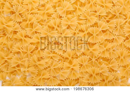 Uncooked bow-tie or farfalle pasta as a background. Delicious, hard, raw and bright yellow texture close up. Tasty traditional farfalle Italian macaroni. Flour products.