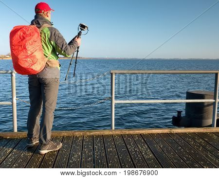 Photographer With Red Backpack On  Wooden Pier Above Sea