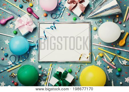 Party or birthday background. Silver frame with colorful balloon gift box carnival cap confetti candy and streamer on vintage blue table top view. Flat lay style. Holiday mockup.