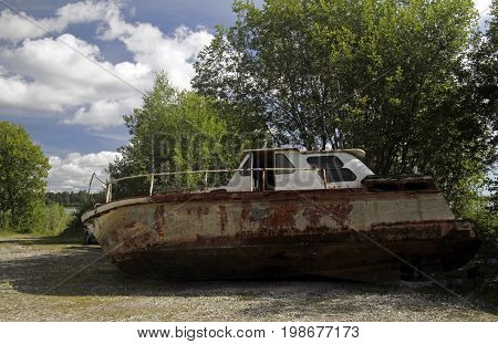 A rusty abandoned boat lying in a field