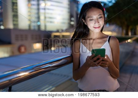 Woman sending sms on cellphone at night